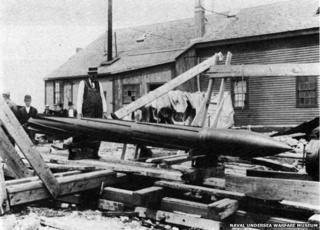 Torpedo lying in street amid damage