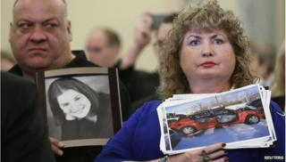 Mary Theresa Ruddy (R), whose daughter Kelly was killed in 2010 when she lost control of her 2005 Chevrolet Cobalt, holds a picture of the vehicle, while her husband Leo (L) holds a photo of their daughter