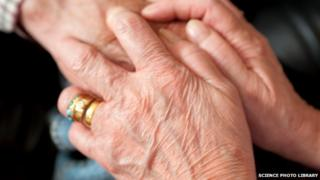 Elderly woman being comforted by a carer who is holding her hands.