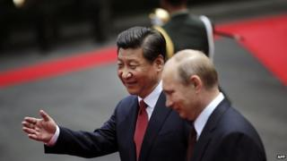 Russia's President Vladimir Putin (R) and China's President Xi Jinping review an honour guard during a welcoming ceremony at the Xijiao State Guesthouse ahead of the fourth Conference on Interaction and Confidence Building Measures in Asia (CICA) summit, in Shanghai on 20 May 2014
