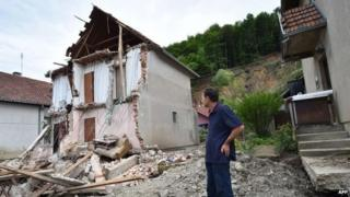 A man stands near his house damaged by flooding and a landslide in Krupanj, Serbia