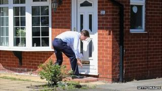 Nick Clegg posting an election leaflet through a door in Stockport