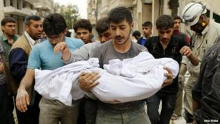 A man carries a dead body after what activists said was a barrel bomb attack by government forces on Aleppo - 25 April 2014