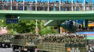 Paramilitary policemen ride on trucks during a parade in central Urumqi (23 May)