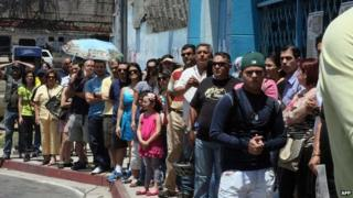 Venezuelans line up to vote in front of a polling station in San Cristobal on 25 May, 2014