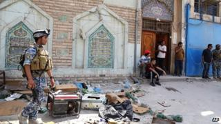 Iraqi security forces and civilians inspect the site of a suicide attack at a mosque in the Shorja market area in central Baghdad