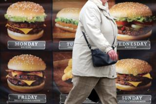 Woman walking past burger shop