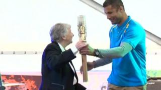 Richard Parks hands the baton to Anne Ellis, president of the Commonwealth Games Council for Wales