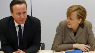 British Prime Minister David Cameron, left, and German Chancellor Angela Merkel speak during a meeting on the sidelines of an EU summit in Brussels on 21 March 2014.
