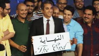 """Egyptian satirist Bassem Youssef, who is known as """"Egypt's Jon Stewart,"""" poses with his team with an English and Arabic placard reading """"the end,"""" during a press conference in Cairo, Egypt, Monday, June 2"""