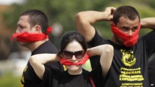 "Federal police wearing T-shirts that read in Portuguese ""SOS Federal Police"" cover their mouths with bandanas in Rio de Janeiro on 7 May, 2014"