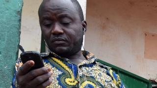 A shopkeeper using a mobile phone in Bangui, CAR - April 2014