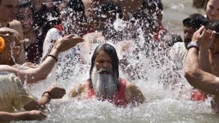 Hindu devotees splash water on a Hindu Sadhu during the Kumbh Mela festival in Haridwar
