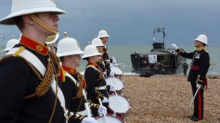 A band from the Royal Marines School of Music plays to welcome a team of Royal Marines as they arrive at Southsea