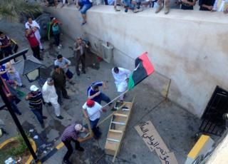 Tripoli protesters smash makeshift coffin scrawled with the names of hardline Islamist militia Ansar al-Sharia and the country's national congress.