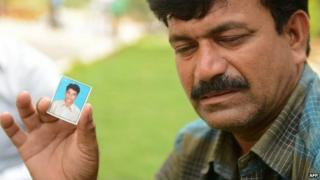"""Banoth Shekar, father of missing student B Rambabu Naik and feared drowned in the Beas River in India""""s northern Himachal Pradesh state, holds a identification photograph of his son."""