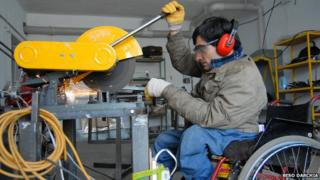 Gela La Ghidze at work in a factory using an angle grinder