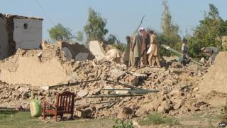 Pakistani tribesmen clear rubble and belongings from their destroyed houses following Pakistan military airstrikes against suspected Taliban hideouts in Miranshah in North Waziristan on 24 May 2014.
