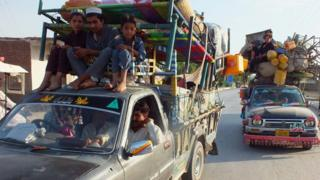 Internally displaced Pakistanis arrive in Bannu, a town on the edge of Pakistan's lawless tribal belt of Waziristan, on 11 June 2014.