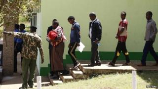 Suspected Somali illegal migrants and refugees arrested in a police swoop arrive at a holding station in Kenya's capital, Nairobi, 7 April 2014