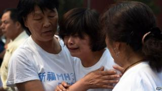 Relatives of passengers on missing Malaysia Airlines flight MH370 cry as they gather at the Lama Temple in Beijing on June 15