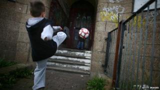 Child kicks ball at run-down building