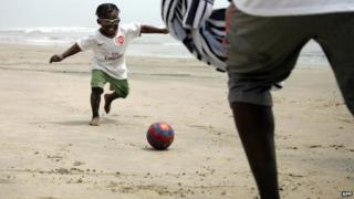 A child plays football with his father at the beach in Accra, Ghana, on 6 February 2008