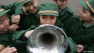 Chinese Army recruits watch as a colleague plays a trumpet