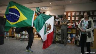 A Mexican fan holds the Mexican and Brazilian flags at Rio's international airport. 10/06/2014