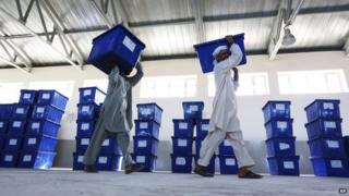 Afghan election workers carry ballot boxes at an election commission office in Jalalabad east of Kabul, Afghanistan