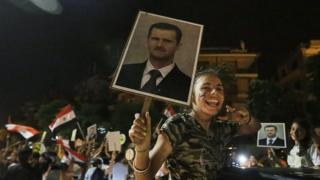 A supporter of Syrian President Bashar Assad celebrates his re-election on 4 June, 2014.