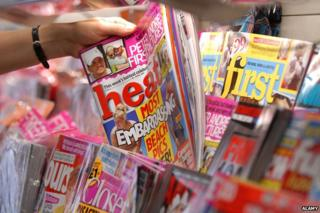 Hand picking gossip mag out of newsagent shelf