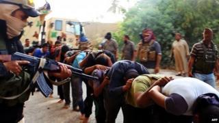 A masked ISIS militant aiming a gun at captured Iraqi men