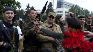 Pro-Russian rebels receive flowers after taking an oath of allegiance
