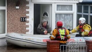 Rescuers help a woman in Rhyl