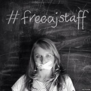 A journalist with taped up mouth against a blackbard with #FreeAJStaff