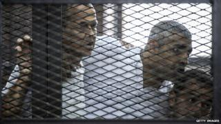Al-Jazeera news channel's Australian journalist Peter Greste (left-right) and his colleagues, Mohamed Fadel Fahmy and Egyptian Baher Mohamed listen to the verdict on 23 June 2014