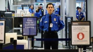 A Transportation Security Administration (TSA) agent waits for passengers to use the TSA PreCheck lane being implemented by the Transportation Security Administration at Miami International Airport 4 October 2011