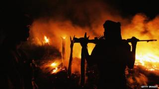 Sudanese rebel fighter and flames