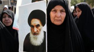 An Iraqi woman living in Iran holds a poster of the Grand Ayatollah Ali al-Sistani during a protest