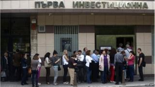 """People queue in front of a branch of Bulgaria""""s First Investment Bank in Sofia on June 27, 2014"""