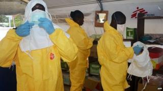 Members of Medecins Sans Frontieres don protective gear at Donka Hospital in Conakry, Guinea. 28 June 2014