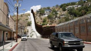 A steel border fence separates Nogales, Arizona, from its sister city in Sonora, Mexico 25 June 2014