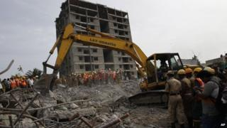 Rescuers, search for workers believed buried in the rubble of a building that collapsed late Saturday during monsoon rains on the outskirts of Chennai, India, Monday, June 30, 2014.