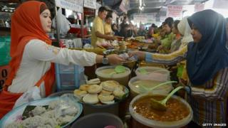 Indonesian women buying food at stall, in headscarves