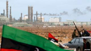 File photo: The Kingdom of Libya flag flies in front of a refinery in Ras Lanuf, 8 March 2011