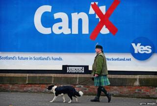Colin MacDonald Provan walks his dog Colleen down Glasgow High Street past a Yes referendum campaign billboard on 20 May, 2014