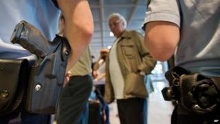 Police guards as passengers queue at the security checkpoint at the Rhein-Main airport in Frankfurt, Germany, Thursday July 3