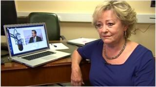 Ann Barnes in front of picture of David Cameron