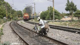 An Indian snacks vendor crosses railway tracks with his bicycle as a train approaches, behind, in Hyderabad, India